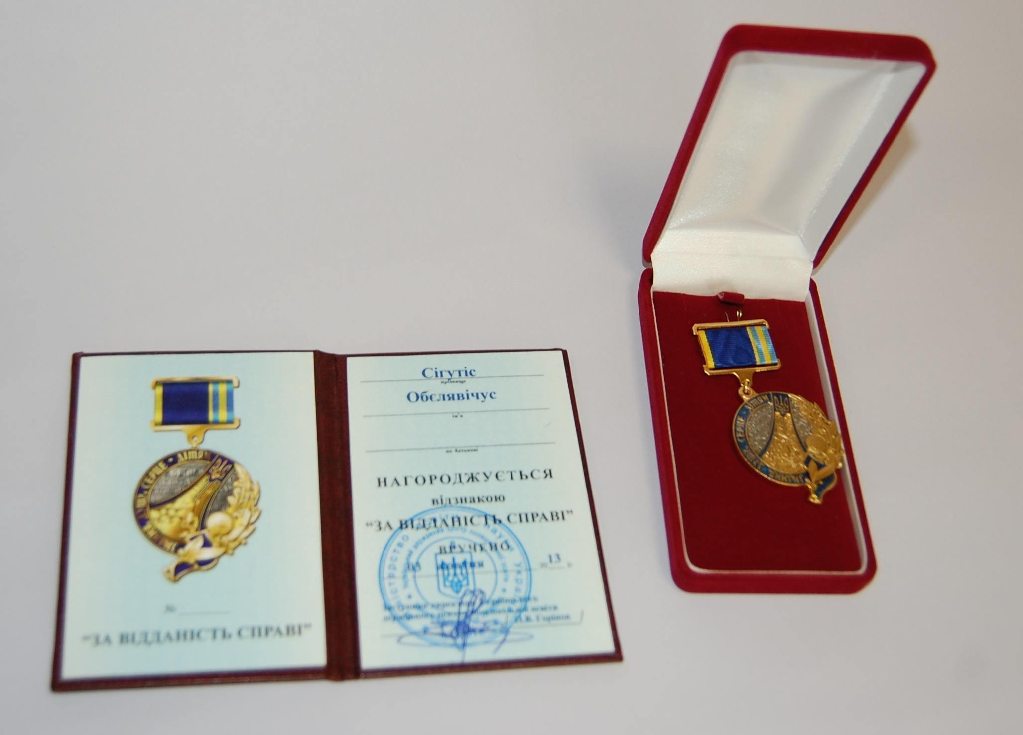 Medalis, įteiktas Sigučiui Obelevičiui, ir jo dokumentas.