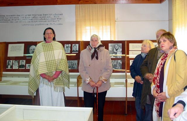 J. Pačinskienė su muziejaus lankytojais prie ekspozicijos.