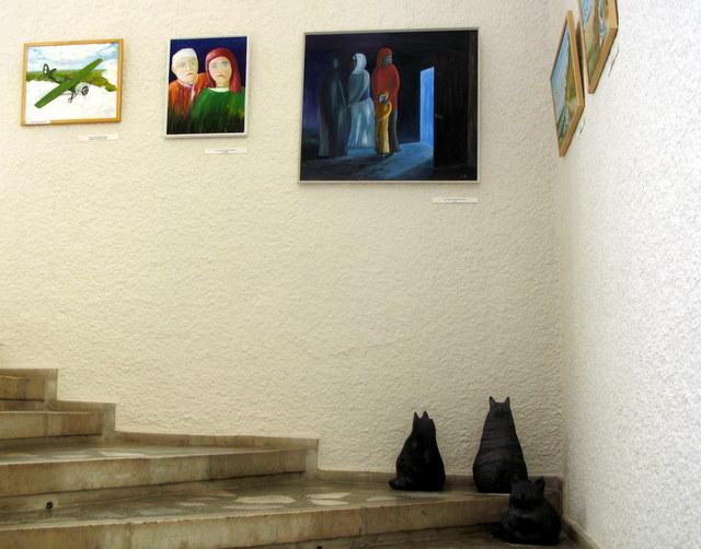 Ant koplyčios laiptų po tapybos ekspozicija sutūpė Skaidrės Račkaitytės moliniai katinai